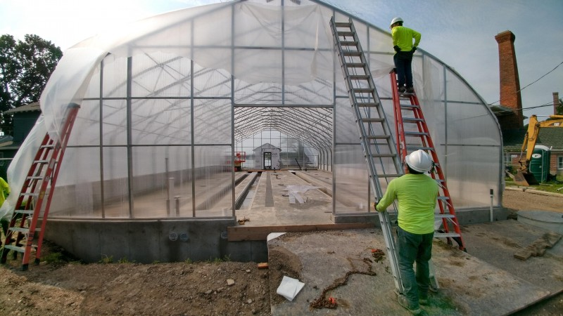 A building frame covered in semi-translucent plastic film, with workers in safety yellow shirts