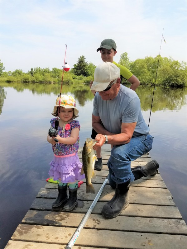Small girl in pink bonnet, holding a fishing rod